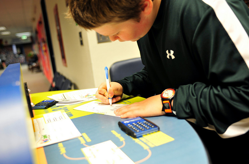 Luke Metzger, 11, fills out his check to enter the money bus.