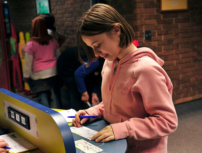 Desiree, 11, fills out her deposit slip before heading to the teller to receive her check and debit card.