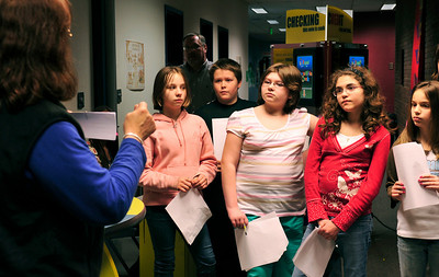 Desiree, 11, Luke Metzger, 11, Charlie, 12, Julie, 10, and Ashton, 11, listen to instructions about writing checks when the Money Bus came to Devaney.