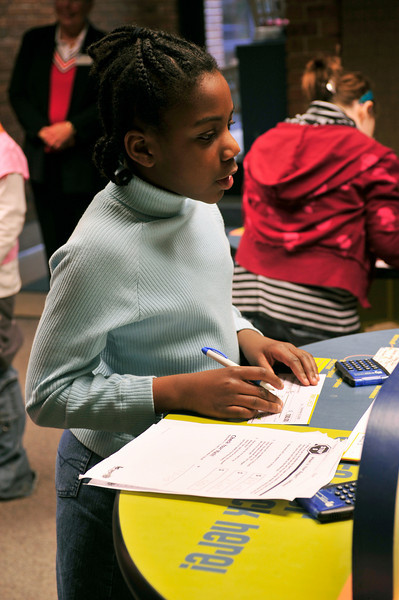 Chyanne, 11, pauses while filling out her deposit slip.