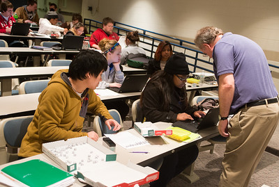 Professor Joseph West uses Papa Johns pizza boxes and dice for a simulation of radioactive decay.