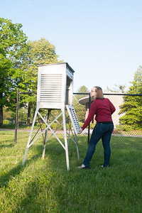 Checking readings at the NORA weather station located north the Fine Arts Building and east of Holmstedt Hall