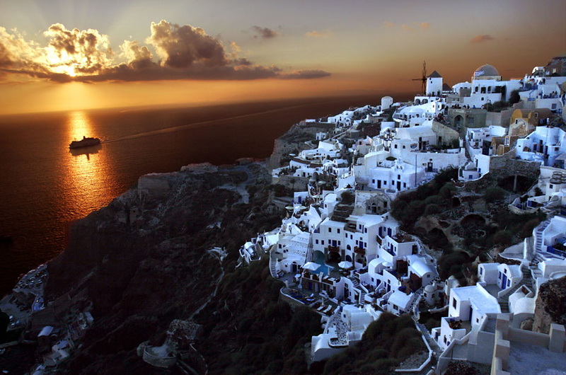 A ferry boat arrives at sunset, Oia, island of Santorini, Greece.