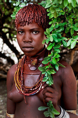 Meet Galtier, a young woman from the Hamer tribe. Galtier is already married at her young age. Her age is unknown to her, as is common with the Ethiopian tribes, however the type of necklace she's wearing indicates that she is the first wife. Her marriage required 'bride wealth', a payment made by her husband's family to her family made up of goats, cattle and guns. Although it's paid over time in installments similar to a bank loan, it's so high (30 goats and 20 head of cattle), that it might not be paid back in a lifetime. Galtier has covered her hair and body with clay, butter and animal fat which is traditional practice among Hamer women.