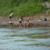 Young girls doing laundry in the river- for when you want to get your clothes 5 percent cleaner and 85 percent wetter than they were before you started.