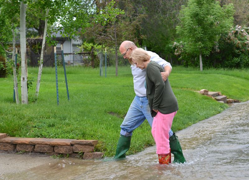 Justin Sheely | The Sheridan Press<br /> Home owners Andy Soule, left, and Denise Soule walk through running water on Schiller Street and Monte Vista in Sheridan Tuesday, May 29, 2018. More than two inches of rain fell over Memorial Day weekend causing area flooding near creeks throughout Sheridan County.
