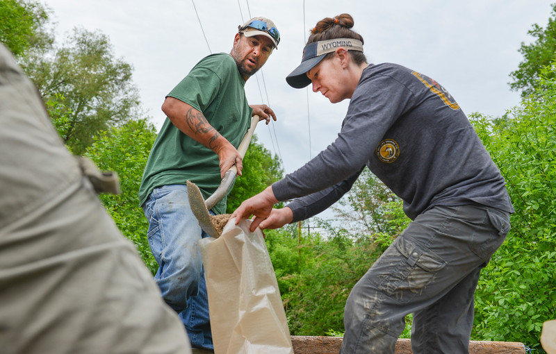 Justin Sheely | The Sheridan Press<br /> Neighbors Boomer Merrill, left, and Kim Hartgrave fill sandbags to reinforce a wall on Monte Vista Street in Sheridan Tuesday, May 29, 2018. More than two inches of rain fell over Memorial Day weekend causing area flooding near creeks throughout Sheridan County.