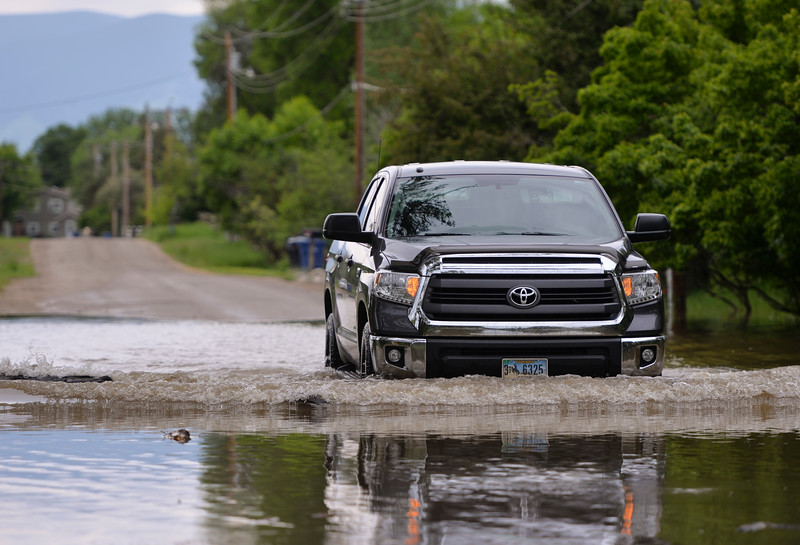 Justin Sheely | The Sheridan Press<br /> A motorist drives through a flooded part of Leopard Street in Sheridan Tuesday, May 29, 2018. More than two inches of rain fell over Memorial Day weekend causing area flooding near creeks throughout Sheridan County.