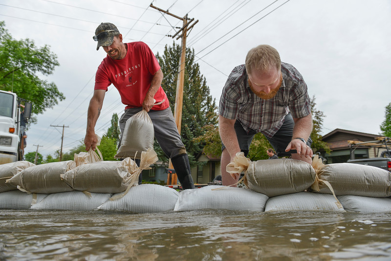 Justin Sheely | The Sheridan Press<br /> Neighbors Ryan Blanchard, left, and Cooley Butler build up a sandbag wall on Monte Vista Street in Sheridan Tuesday, May 29, 2018. More than two inches of rain fell over Memorial Day weekend causing area flooding near creeks throughout Sheridan County.