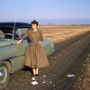 Dorothy Pape (my mom) standing next to my dad's car, typical farm road c.1958