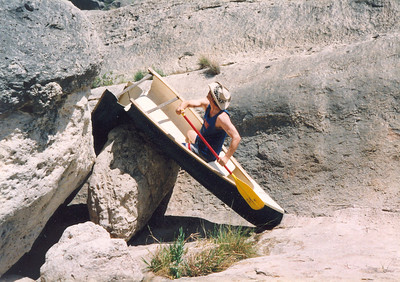 CANOE BOY -- PECOS RIVER 1994 Before leaving Dallas for the last time, I went on a week-long canoe trip down the Pecos River from Pandale to the Amistad Reservoir with some photography buddies. When we reached Rainbow Rapids -- a rather severe and intimidating chute -- we came across this canoe that some other folks decided to leave here. Boy, wouldn't you have loved to seen that? It made for a great photo op, I think.