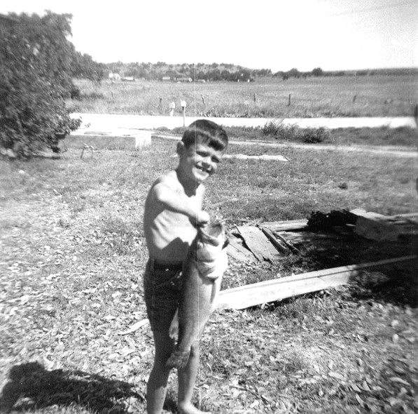 "THE BIG CATCH -- JULY 1958 Would you look at the size of that thing! I was fishing with a small 7-year-old-sized cane pole and this big bastard hit my minnow and snapped my pole in half. That I didn't drop pole, fish, and all in fright is a major miracle in itself. As it was, I ran barefoot back up the shore to my folks, trailing my fish along behind me in the dirt, and screaming, <i>""He broke my pole! He broke my pole!""</i> through huge rivers of tears. Of course he broke your pole, Doug. Good God, look at this thing! It's HUGE!!!"