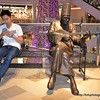 Man sitting on a bench next to a statue of a Turkish man with a fez and playing a musical instrument at Terminal 21 Shopping Centre in Korat, Thailand in August 2017