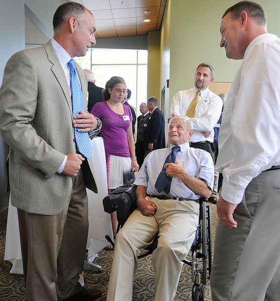 Mike Bordick ,left , Dan Kane , right, spend a few minutes with John Winkin at a tribute to him and his coaching career Saturday at the U of Maine in Orono. Dr Winkin is accompanied by his son David and his granddaughter Bethany.  Bangor Daily NEws/Michael C. York