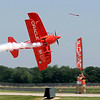 Sean Tucker flies his Team Oracle biplane on edge as he cuts a ribbon during Saturday's air show.