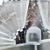 "Paul Hughes from Eden Prairie shaves a block of ice that would later become an angel's head on Saturday. Because of the warmer temperatures, Deneena Hughes said, ""The wall (of ice) was completely falling forward,"" and explained that they had to shove shims underneath it to keep it upright. The Hughes' and three other teams are in a friendly ice sculpture competition at Kiwanis Holiday Lights in Sibley Park. The winners, as voted by the public, will receive $500. Photo by Jackson Forderer"