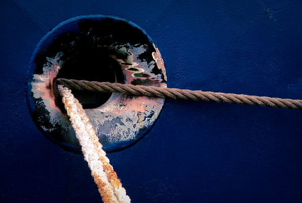 A porthole on the side of a tall ship, moored at a dock in Philadelphia.