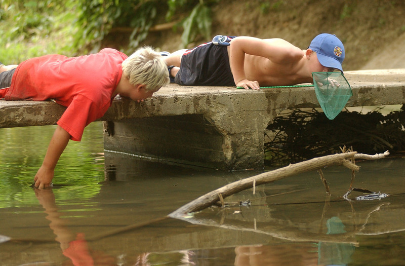 E.L. HUBBARD/JOURNALNEWS<br /> Jake Buchanan, 9, left, and Tony Dyer, 10, hunt for crawdads in Shaffers Run in Hamilton, Ohio Friday, June 25, 2004. The boys said they planned to use them for fish bait.