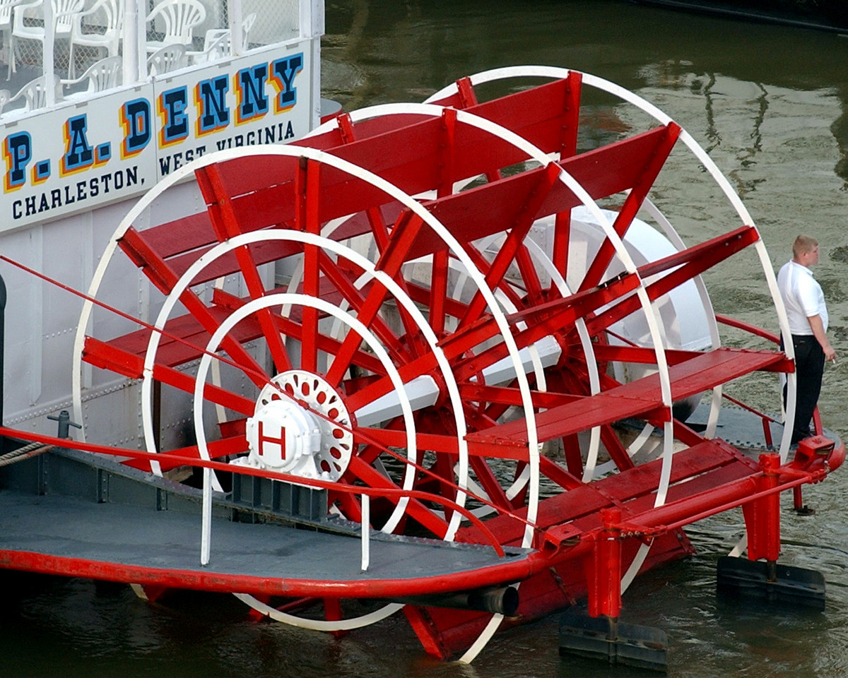 E.L. HUBBARD/JOURNALNEWS<br /> A worker takes a break next to the paddle wheel of the P.A. Denny, from Charleston, West Virginia, while it is docked in Cincinnati for Tall Stacks Thursday, 10/16/03.