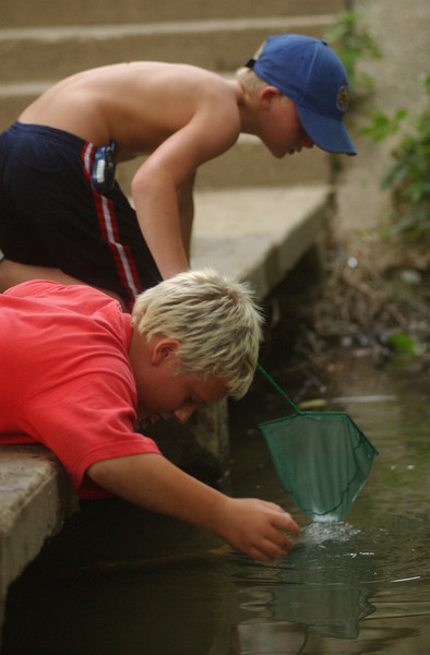 E.L. HUBBARD.JOURNALNEWS<br /> Jake Buchanan, 9, foreground, and Tony Dyer, 10, hunt for crawdads in Shaffers Run in Hamilton, Ohio Friday, June 25, 2004. The boys said they planned to use them for fish bait.