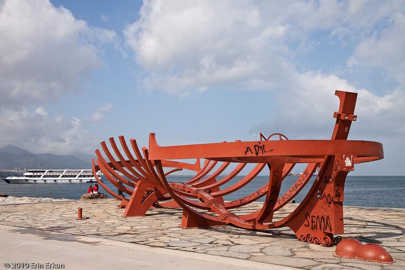 "20 April 2010<br /> Konak - A modern sculpture entitled ""Asırlardır Tekne"" (roughly, Craft of the Ages) - by Bihrat Mavitan.  Too bad people have seen fit to scribble graffiti on it."