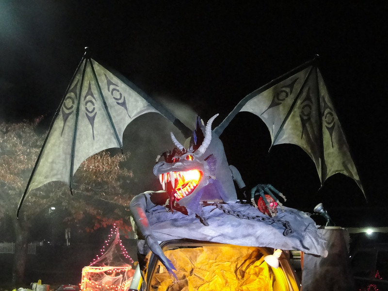 "Halloween ""Trunk-Or-Treat"" Display.  Fun ""full-size"" dragon construction for school event.  Over 12 foot wingspan.  Lighting effects and ""fire"" breathing effect was a hit of the event.  Budget minded project of scrap lumber, dollar store finds and discount fabric.  Sculpted head of paper mache material."