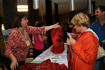 Pam Milczarski hands out registration bags to the South Dakota contingent.