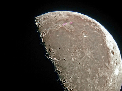 Image of the moon in 8 inch reflector telescope. Notice red fringes above made by camera.