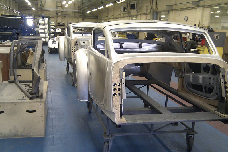 Each body is a sandwich of an ash frame with riveted and hot bonded aluminium panels on each side.   The curved and sculpted panels are made by blowing hot aluminium panels against a mould.