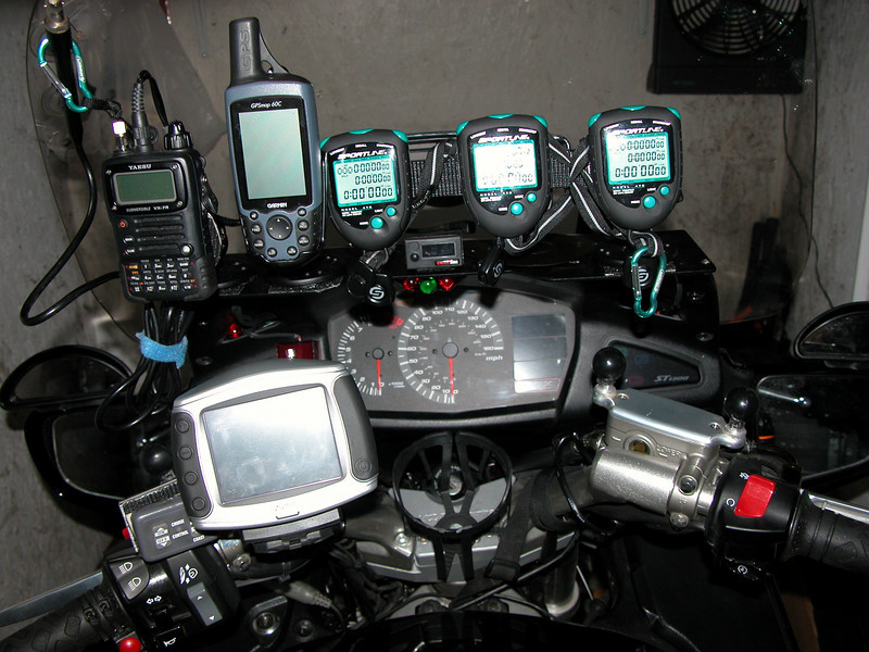 2006 Honda ST1300 cockpit.  Up top left to right; ham radio, GPS for race data (average speed, mile data, elevation), 3 stop watches.  A GPS down below for map info, with a cup holder right below the speedometer.
