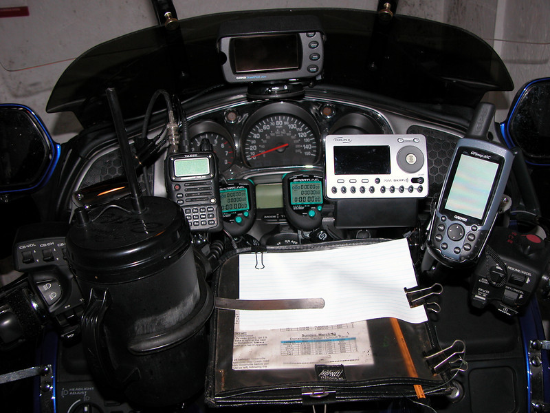 The view of my Gold Wing Cockpit. L to R is a cold drink (water), ham radio, 2 stop watches, XM-Radio (for the trip to and from the race), GPS on the right for race data (average speed, altitude, current speed) with a GPS in the middle for all the map info.  And then a mini-clipboard to write down rule infractions during the bicycle race.