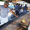 Globe/T. Rob Brown<br /> Dusty Cook, of Lamar, and Lamar Metro Club member, pours red sauce over barbecue ribs on the rack Thursday morning, Aug. 23, 2012, during the annual Lamar Free Fair in downtown Lamar.