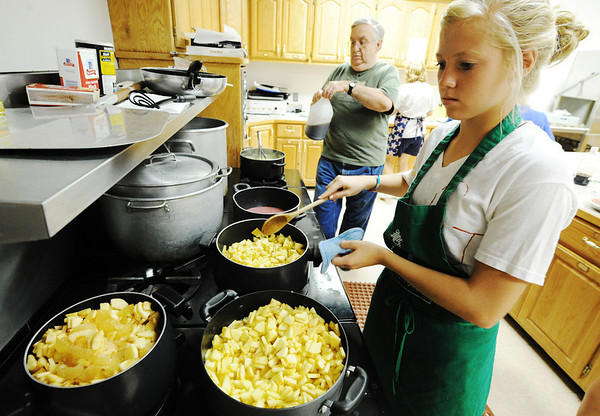 Globe/T. Rob Brown Taylor Beck, 16, of Carl Junction, cooks apple slices for the Fall Fiasco Pie Sale recently. Ivan Obert, of Joplin, works on coconut cream pie in the background.