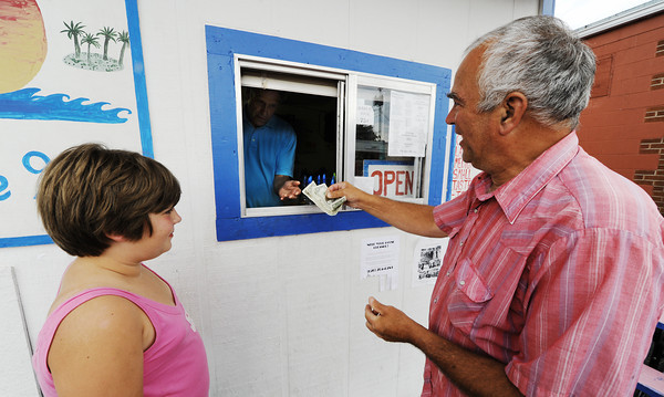 Globe/T. Rob Brown<br /> Customers Jeff Lee, right, and his granddaughter Abby Lee, both of Pittsburg, Kan., purchase two Hawaiian shaved ice refreshments from owner-manager David Schaper, of Cherryvale, Kan., Thursday evening, July 26, 2012, at the Tropical Snow station in Pittsburg.