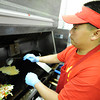 Globe/T. Rob Brown<br /> Ge Xiong, owner of New Day Cafe in Joplin, tops browning hashbrowns with eggs. The Monster Mess includes scrambled eggs, hasbrowns and cheese plus a mix of mushrooms, onions, green peppers, tomatoes, sausage and ham.