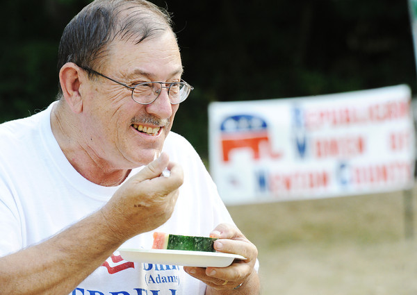 Globe/T. Rob Brown<br /> J.C. Herrell, of Neosho, husband of Billie (Adams) Herrell, who is running for Newton County Public Administrator, smiles after eating a piece of juicy watermelon Tuesday evening, July 31, 2012, during the annual Republican Women of Newton County watermelon feed in Neosho's Big Spring Park.