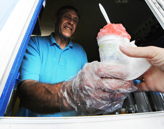Globe/T. Rob Brown<br /> Owner/Manager David Schaper, of Cherryvale, Kan., hands a Tiger Blood flavor Hawaiian shaved ice to a customer Thursday evening, July 26, 2012, at his Tropical Snow station in Pittsburg.