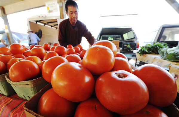 Globe/T. Rob Brown Nhia Xiong, owner of Nhia & Ying Xiong produce of Anderson, arranges tomatoes Friday morning, June 29, 2012, at the Webb City Farmers' Market.