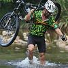 Mountain biker wading through a river, Borneo