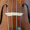 Close-up violin front with strings, bridge, fine tuner, f-holes and side curves.  Violin maker unknown.  Mid-19th c