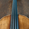 Close-up violin front shoulders, neck, fingerboard on worn wood background.  Violin maker unknown.  Mid-19th c
