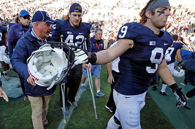 Penn State linebacker Michael Mauti (42),of crutches, follows running back Michael Zordich (9) off the field after a 45-22 win over Indiana in an NCAA college football game in State College, Pa., Saturday, Nov. 17, 2012. Mauti was injured on a play in the first quarter of the game. (AP Photo/Gene J. Puskar)