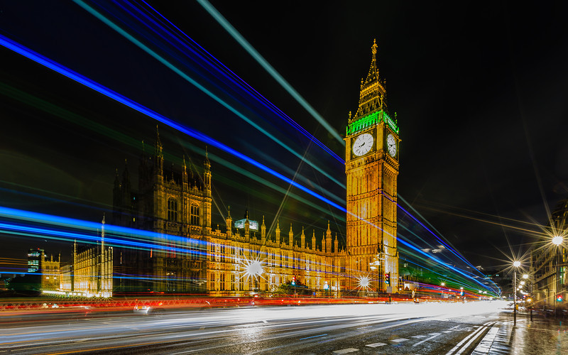 Big Ben and Westminister in London with double-decker bus and vehicle trails