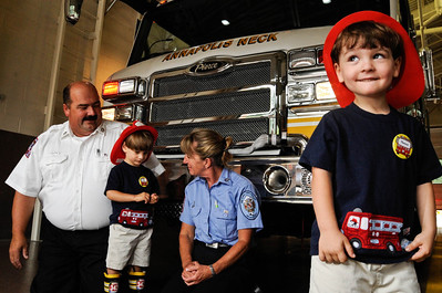 James, left, and Thomas Martino 3 celebrated their third birthday at the firestation.  Lt. Richard Jones, left, and fire fighter Debbie Sosnosk give them a tour of the Annapolis Neck Fire Station. (Shannon Lee Zirkle) 8/12/09