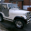 My Jeep CJ5 left front view. Glass body. All stainless steel accessories. Looks much better with the top off.