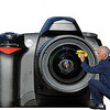 a man in a suit cleans the lens of a giant camera which has a finger print on the lens. Isolation on white background