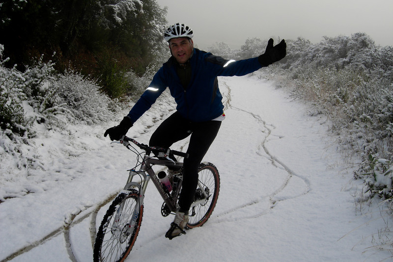 This is a couple years ago during a rare snowstorm in the Santa Cruz Mountains. I was headed out the door to drive up to the summit in my truck when the phone rang. It was a friend who wanted me to ride up the trail with him on our mountain bikes. It didn't take much for him to convince me to make an adventure out of it. It took forever to slog up the hill, it was like riding in wet cement most of the way. We weren't the first ones on the trail as we were following in another riders tracks. About 2/3 of the way up the hill the person in front of us turned around so we were riding in virgin snow the last third of the hill. The sun poked out a few times as we neared the top and the wind had all but died down. It was pretty and spectacular to see our local trail covered in snow. We hung out at the helicopter landing pad and checked out the view before heading down. The ride down was more exciting than the ride up as the steep slope made the trail extremely slippery. It turned out it was quite the ride, cold, wet and slick for us fair weather riders. Quite a few of our local rider friends were a bit jealous when we told them we had played hooky from work to ride in the snow. Definitely worth the effort!