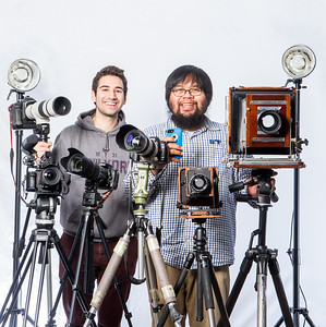University Relations photographers Zayn Roohi and JR Ancheta pose for a portrait with all of their cameras.