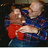 Doc holds infant Nicholas wearing Pats sweater