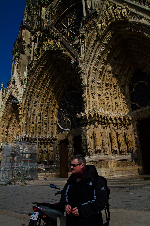 Me in front of Reims (pronounced with a nasally R, Rrraaahnce) Notre Dame Cathedral. The wind is cold enough to chill your fingers thoroughly, painfully in just 5 minutes. The upside, no tourists :D